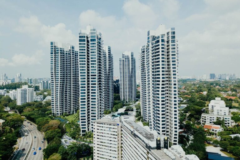 5 high rise buildings with the sky and city in the background