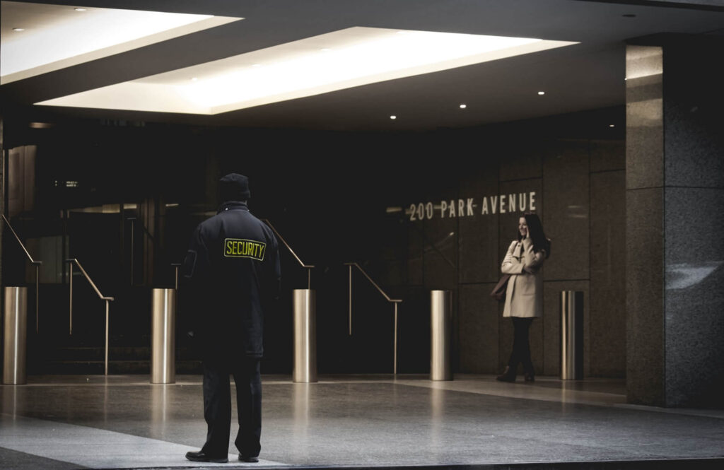 unarmed temporary security guard standing outside of a high rise commercial building