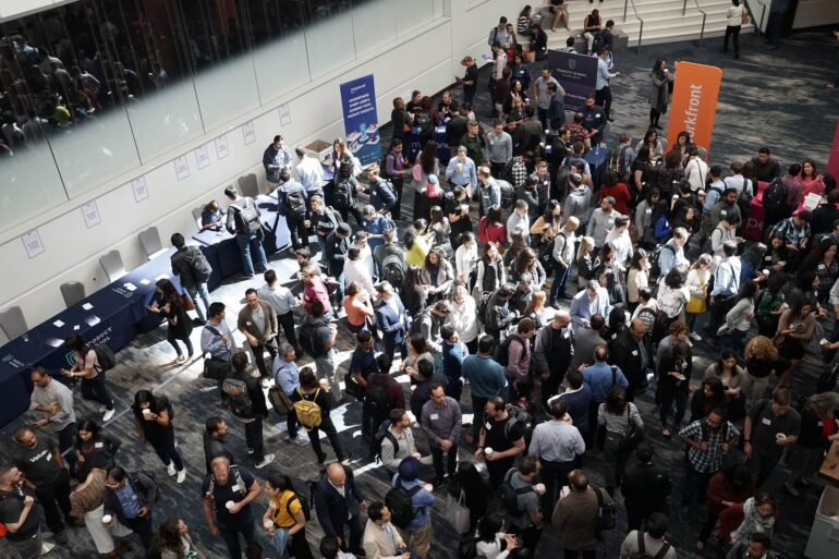 Group of people at a convention or trade show going through a security check point