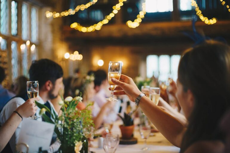 Group of people celebrating a special event and raising their glasses to toast