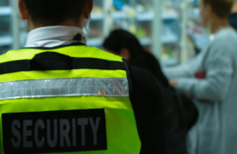 Security guard standing at his post at a retail store watching customers checkout